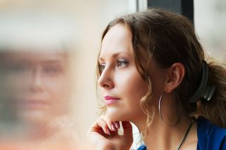 Woman sitting looking out a window