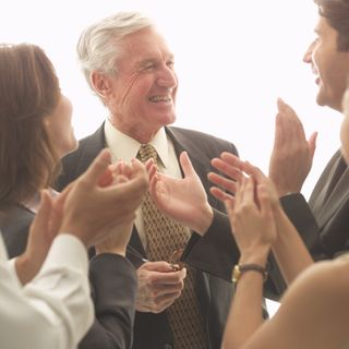 Group of people clapping and smiling with one another